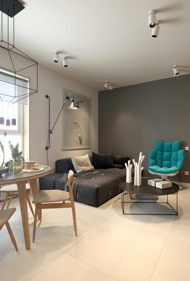 Sala moderna com poltrona azul tiffany e sofá preto.