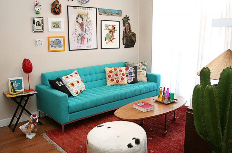 Sala moderna com quadros, cacto e sofá azul tiffany.