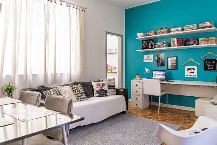 Sala com decoração neutra e parede azul tiffany.