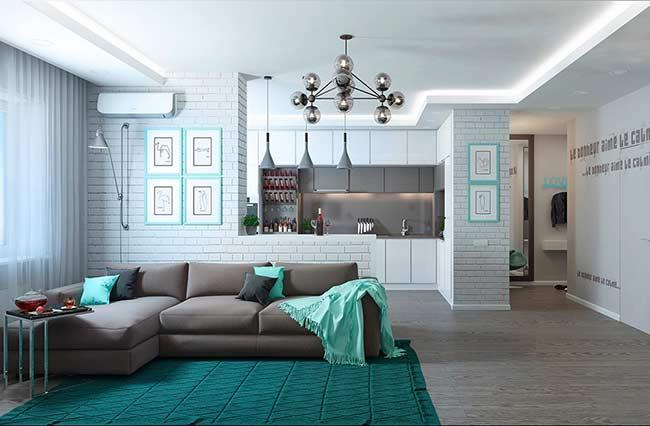 Sala moderna com sofá em L e papel de parede com estampa de tijolinho branco.