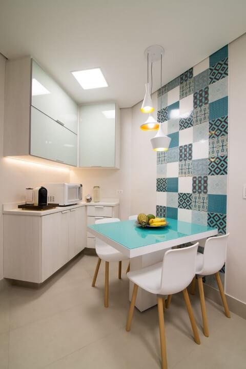 Cozinha pequena com mesa com tampa de vidro.