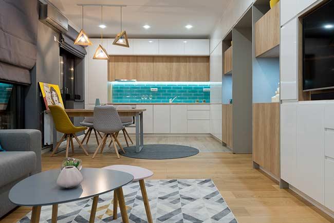 Sala de estar e sala de jantar integrada com decoração moderna e neutra.