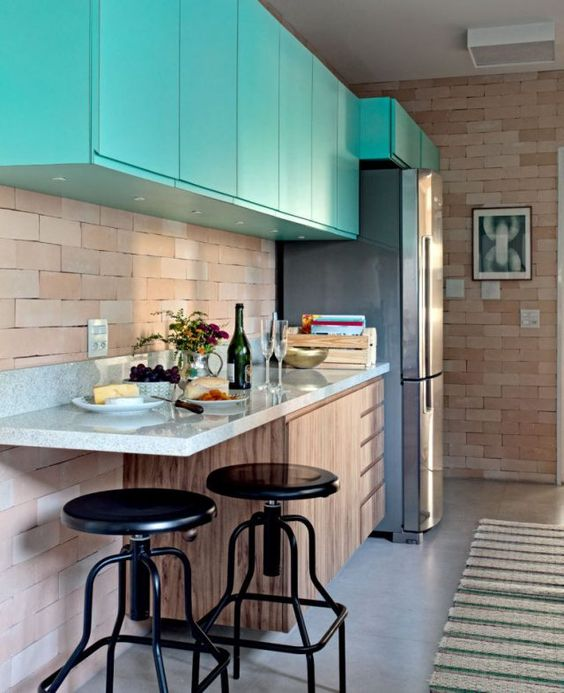 Cozinha aberta com parede de tijolinho aparente.