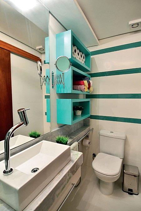 Banheiro pequeno decorado com nichos.