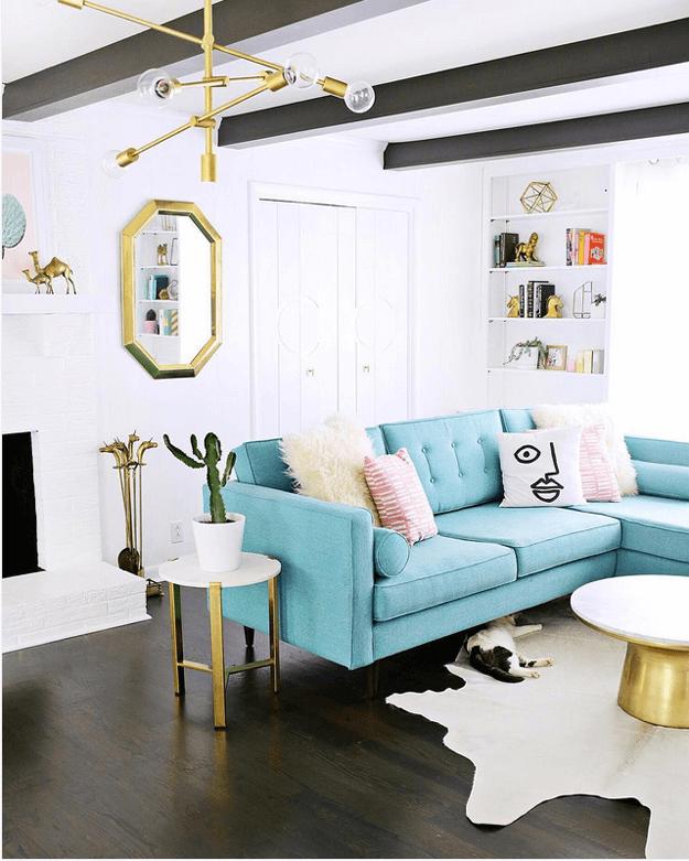 Sala moderna tumblr com mesa lateral dourada e cacto.