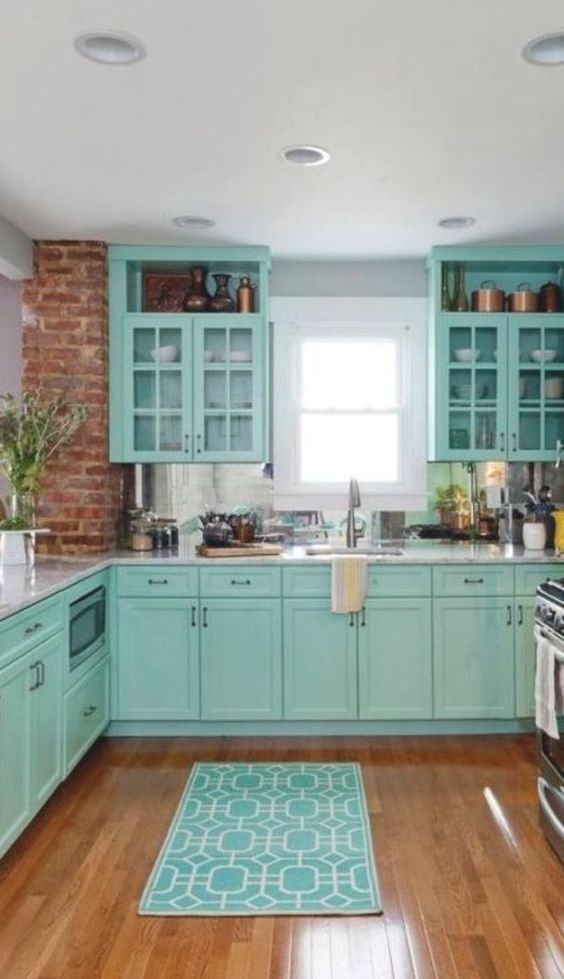 Cozinha com armário clássico e parede de tijolinho aparente.