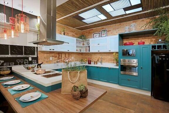 Cozinha em U com mesa de madeira e parede de tijolinho aparente.
