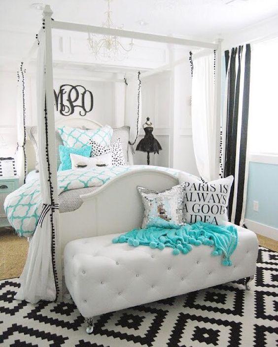 Quarto luxuoso com lustre e decoração preta e branca.