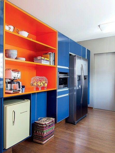 Cozinha aberta moderna com combinação de cores azul e laranja.