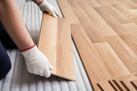 Pessoa de luva instalando piso laminado.