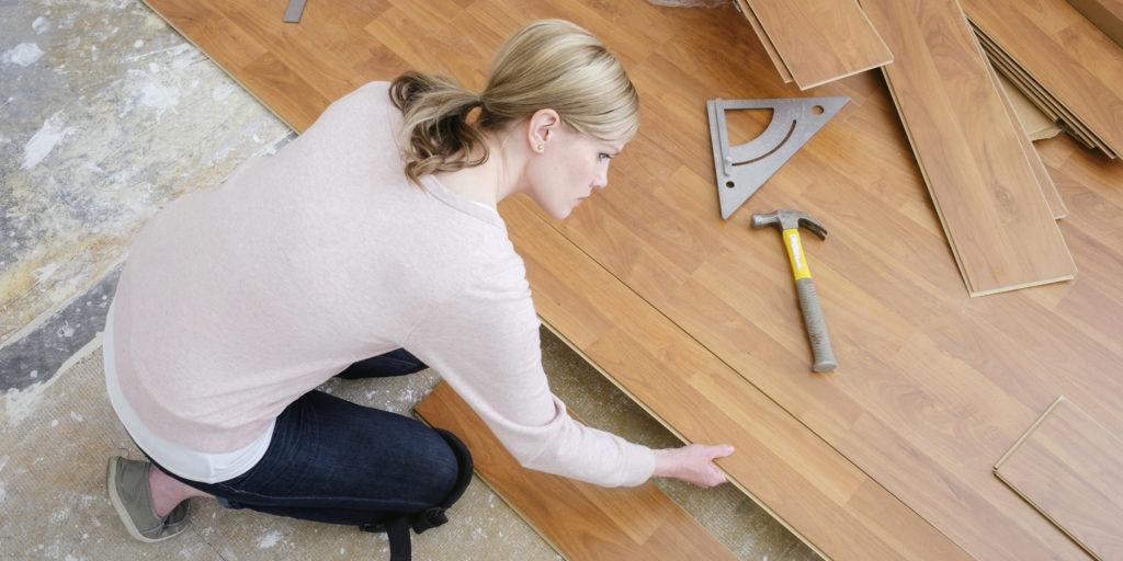 Mulher ensinando como colocar piso laminado.