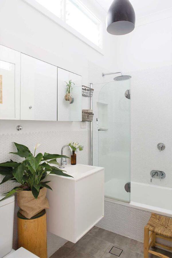 Banheiro branco decorado com plantas.
