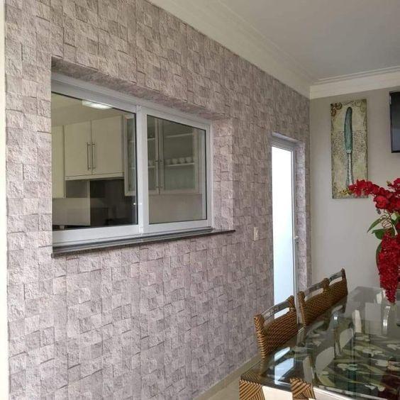 Sala de jantar simples com parede com estampa de pedra.