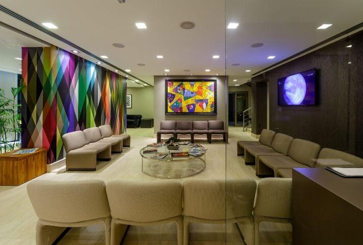 Sala de espera com decorada neutra e parede colorida.