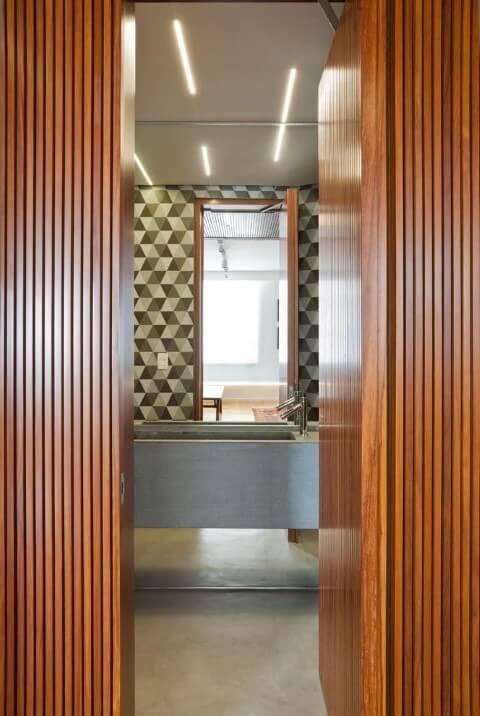 Banheiro moderno com pia esculpida e porta de madeira.