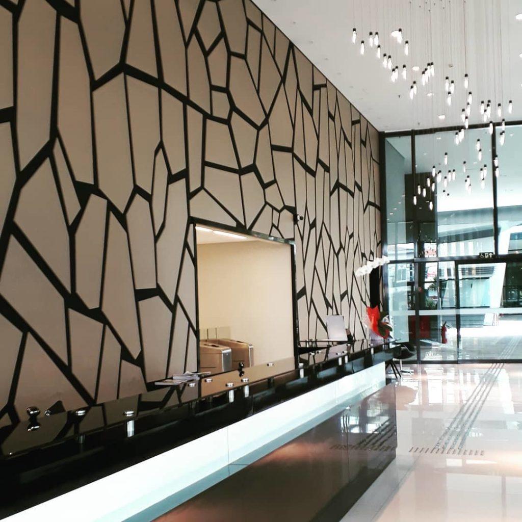Hall de entrada com parede decorada com estampa que imita pedra.