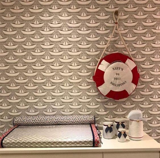 Quarto de bebê com parede decorada com estampa de barcos de papel.