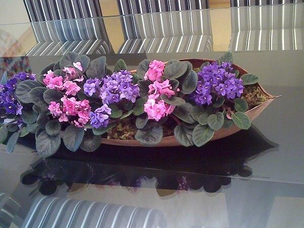 Arranjo de mesa com violetas.