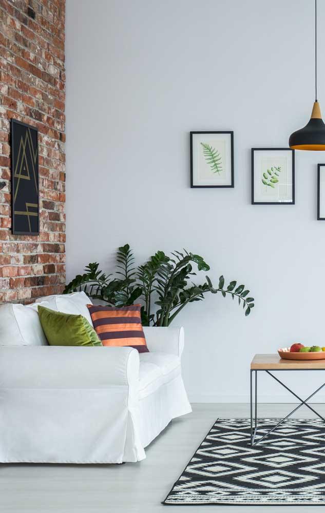 Sala simples com parede de tijolinho.