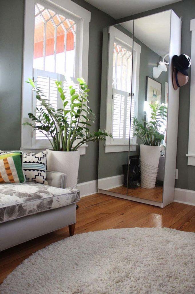 Sala com decoração simples e armário espelhado.
