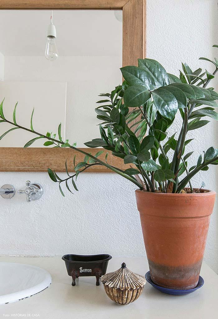 Banheiro decorado com vaso de cerâmica com plantas.