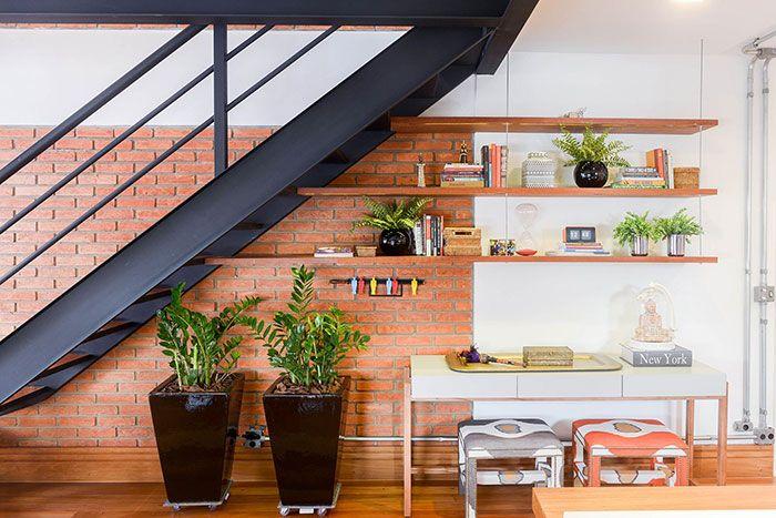 Decoração embaixo da escada com escrivaninha e vasos de plantas.
