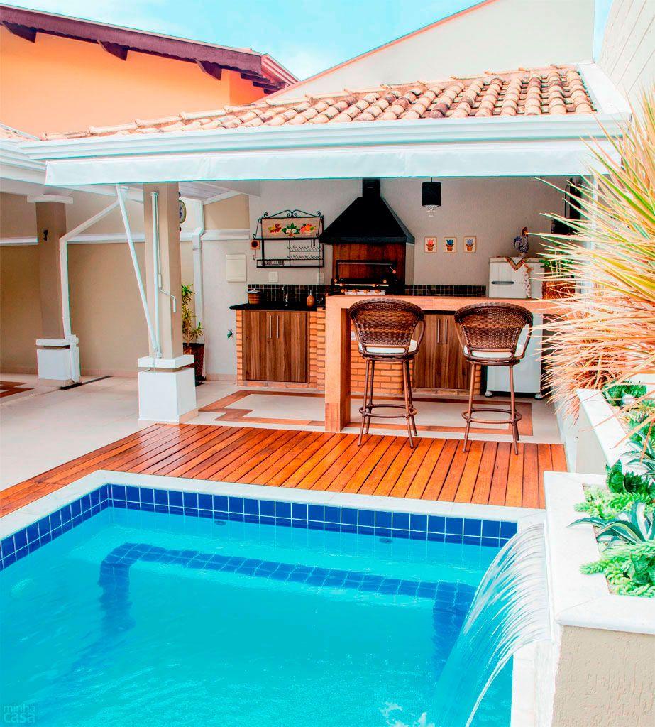 Área de churrasqueira com piscina e balcão de madeira.