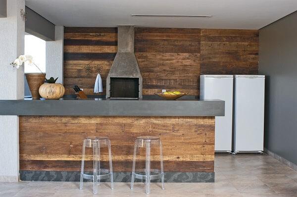 Área de churrasqueira moderna com revestimento que imita a madeira.