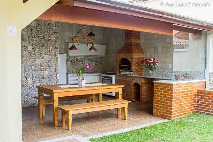 Área de churrasqueira rústica com mesa de madeira.
