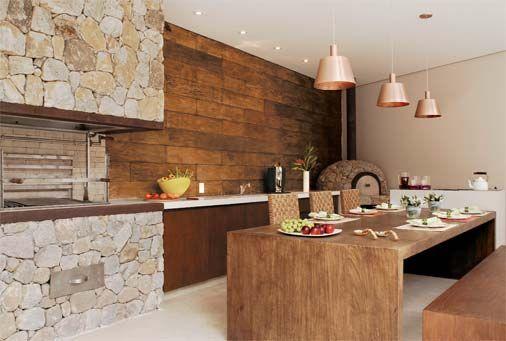 Área de churrasqueira rústico com mesa de madeira.