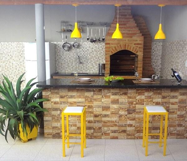 Área de churrasqueira com balcão e lustre pendente amarelo.