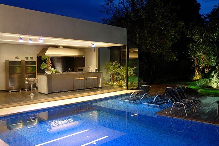 Área de churrasqueira moderna com piscina.