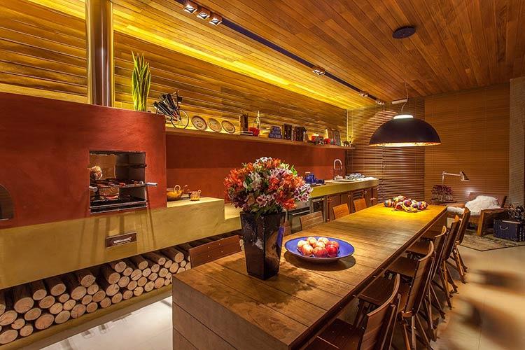 Área de churrasqueira rústica com revestimento vermelho e amarelo.