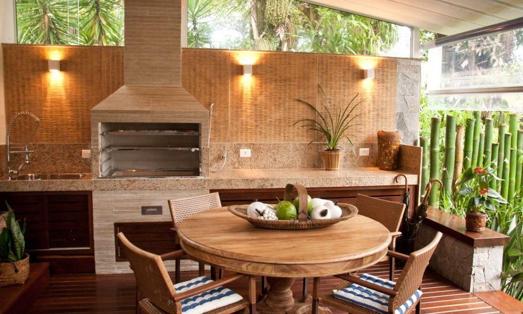 Área de churrasqueira com bancada de granito e mesa redonda.