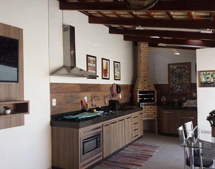 Área de churrasqueira simples com armário de madeira.