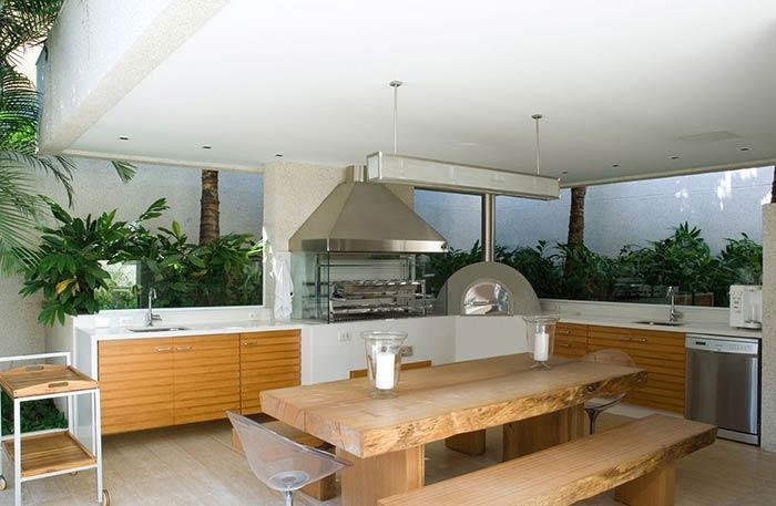 Varanda com mesa de madeira e cozinha.