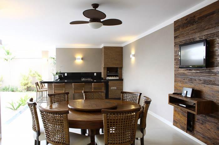 Espaço gourmet com mesa de madeira.