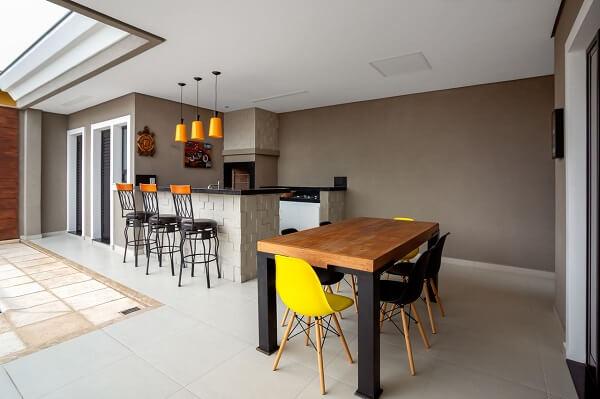 Espaço gourmet com mesa de madeira e cadeiras modernas.