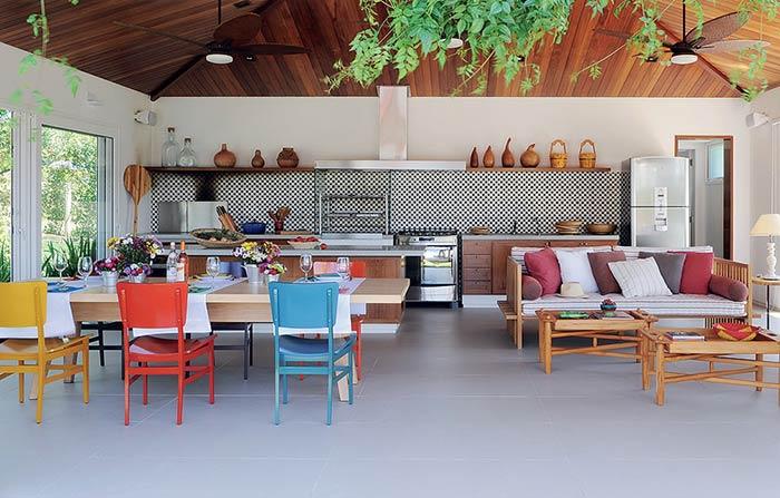 Espaço gourmet com revestimento xadrez e cadeiras coloridas.