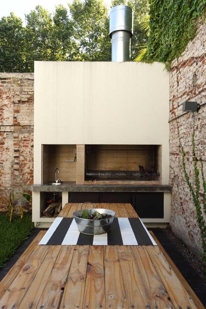 Área de churrasqueira pequena com mesa rústica de madeira.