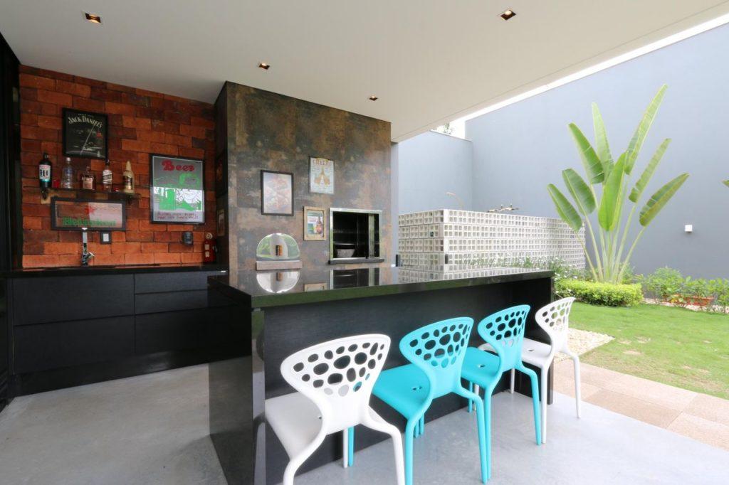 Espaço gourmet com cadeiras coloridas e revestimento de pedra.