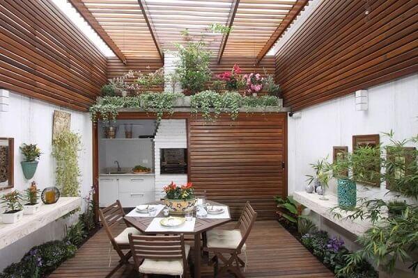 Espaço gourmet com piso e cobertura de madeira.