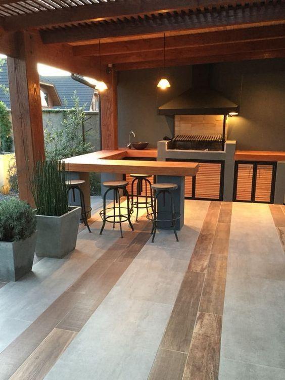 Área de churrasqueira moderna com bancada de madeira.