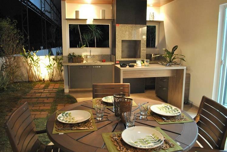 Espaço gourmet pequeno com bancada simples e mesa redonda.