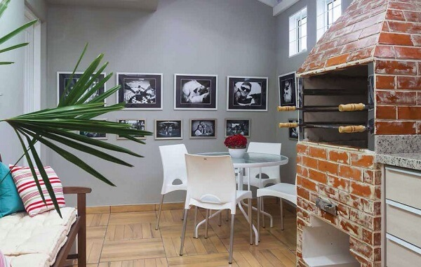 Área de churrasqueira pequeno decorado com quadros.