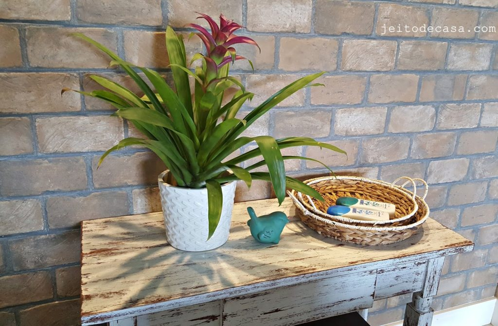 Vaso de bromélia decorando mesa rústica.