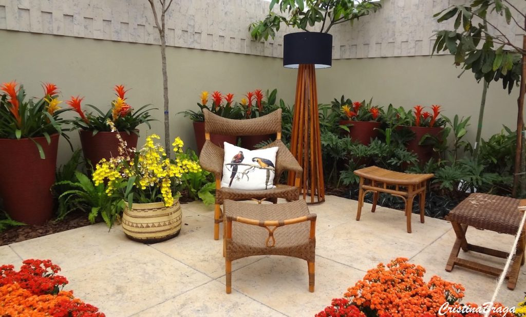 Jardim com plantas e área de descansa.