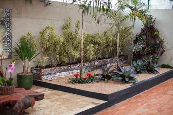 Jardim com bromélias e areia.