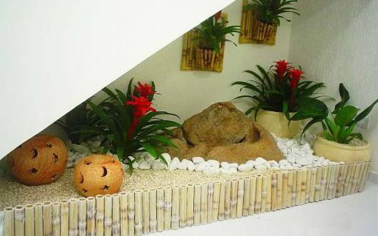 Jardim de inverno debaixo da escada com pedras brancas.
