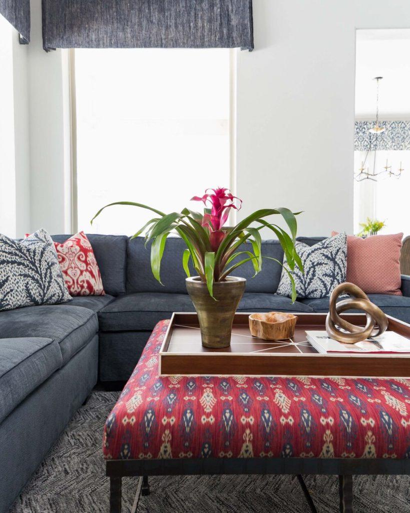 Sala de estar com sofá em L e vaso de bromélia.